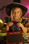 Halloween party with a child holding sign - stock photo
