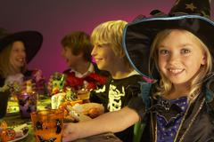 Halloween party with children having fun in fancy costumes - stock photo