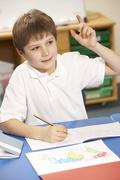 Schoolboy Studying In Classroom Stock Photos
