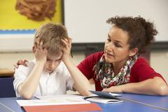 Stock Photo of Stressed Schoolboy Studying In Classroom With Teacher