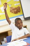 Schoolboy Raising Hand In Classroom Stock Photos