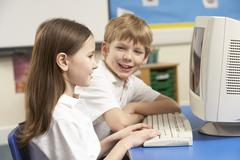 Schoolchildren In IT Class Using Computer Stock Photos