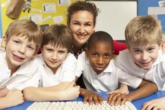 Schoolchildren in IT Class Using Computers with teacher Stock Photos