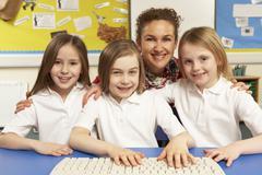 Koululaiset IT luokan tietokoneiden kanssa naispuolinen opettaja Kuvituskuvat
