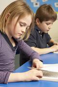 Schoolgirl Reading Book In Classroom - stock photo