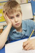 Stressed Schoolboy Studying In Classroom Stock Photos