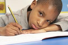 Unhappy Schoolboy Studying In Classroom - stock photo