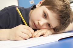 Unhappy Schoolboy Studying In Classroom Stock Photos