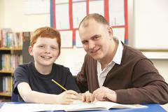 Male Pupil Studying in classroom with teacher - stock photo