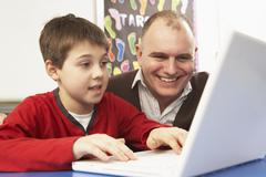 Schoolboy In IT Class Using Computer With Teacher Stock Photos