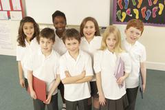 Portrait Of Schoolchildren Standing In Classroom Stock Photos