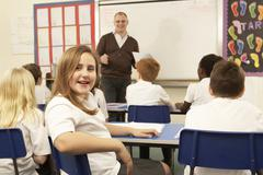 Schoolchildren Studying In Classroom With Teacher Stock Photos