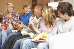 Group Of Teenage Friends Sitting On Sofa At Home Eating Fast Foo Stock Photos