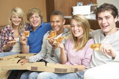 Group Of Teenage Friends Sitting On Sofa At Home Eating Pizza - stock photo