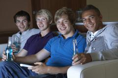 Group Of Teenage Boys Sitting On Sofa At Home Watching Drinking Alcohol Stock Photos