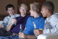 Group Of Teenage Boys Sitting On Sofa At Home Watching Drinking Stock Photos