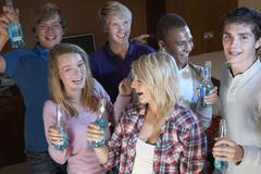 Group Of Teenage Friends Dancing And Drinking Alcohol Stock Photos