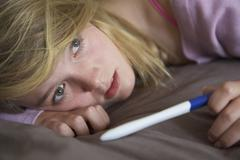 Depressed Teenage Girl Sitting In Bedroom With Pregnancy Test - stock photo