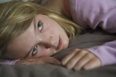 Depressed Teenage Girl Lying In Bedroom - stock photo