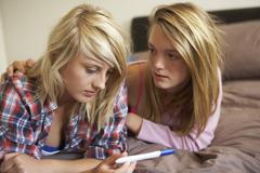 Two Teenage Girls Lying On Bed Looking At Pregnancy Testing Kit - stock photo