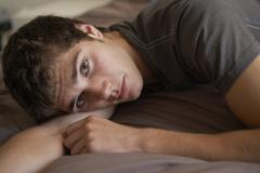 Depressed Teenage Boy Lying In Bedroom - stock photo
