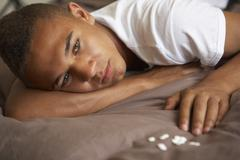 Depressed Teenage Boy Lying In Bedroom With Pills - stock photo
