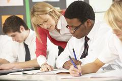 Teenage Students Studying In Classroom With Teacher Stock Photos