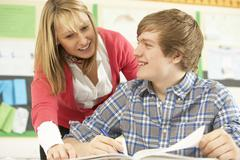 Male Teenage Student Studying In Classroom With Teacher - stock photo