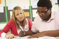 Male Teenage Student Studying In Classroom With Teacher Stock Photos