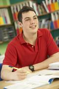 Teenage Male Student In Working In Classroom - stock photo
