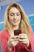 Female Teenage Student Using Mobile Phone By Lockers In School Stock Photos