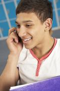 Male Teenage Student Using Mobile Phone By Lockers In School - stock photo