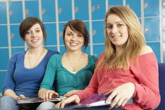 Female Teenage Students Relaxing By Lockers In School Stock Photos