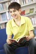 Male Teenage Student In Library Reading Book - stock photo
