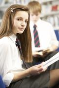 Female Teenage Student In Library Reading Book - stock photo