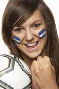 Young Female Sports Fan With Honduras Flag Painted On Face - stock photo