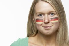 Young Female Sports Fan With German Flag Painted On Face - stock photo
