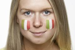 Young Female Sports Fan With Italian Flag Painted On Face - stock photo