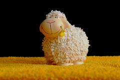 Cheerful smiling lamb with a flower in a mouth Stock Photos