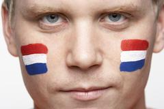 Young Male Sports Fan With Dutch Flag Painted On Face - stock photo