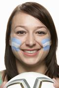 Young Female Football Fan With Argentinian Flag Painted On Face - stock photo