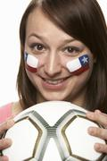 Young Female Football Fan With Chilean Flag Painted On Face - stock photo