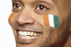 Young Male Sports Fan With Ivory Coast Flag Painted On Face - stock photo