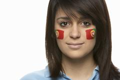 Young Female Sports Fan With Portugese Flag Painted On Face - stock photo