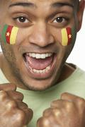 Young Male Sports Fan With Cameroon Flag Painted On Face - stock photo