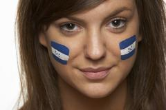 Young Female Sports Fan With Honduran Flag Painted On Face - stock photo