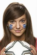Young Female Football Fan With Uruguayan Flag Painted On Face - stock photo