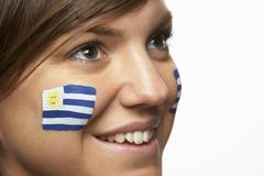 Young Female Sports Fan With Uruguayan Flag Painted On Face - stock photo