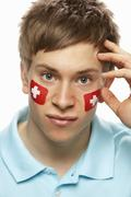 Disappointed Young Male Sports Fan With Swiss Flag Painted On Face Stock Photos
