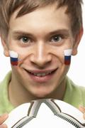 Young Male Football Fan With Slovakian Flag Painted On Face - stock photo